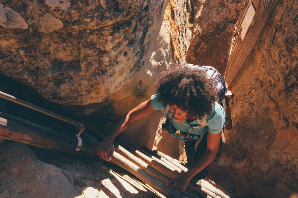 African American woman climbs a ladder at Mesa Verde