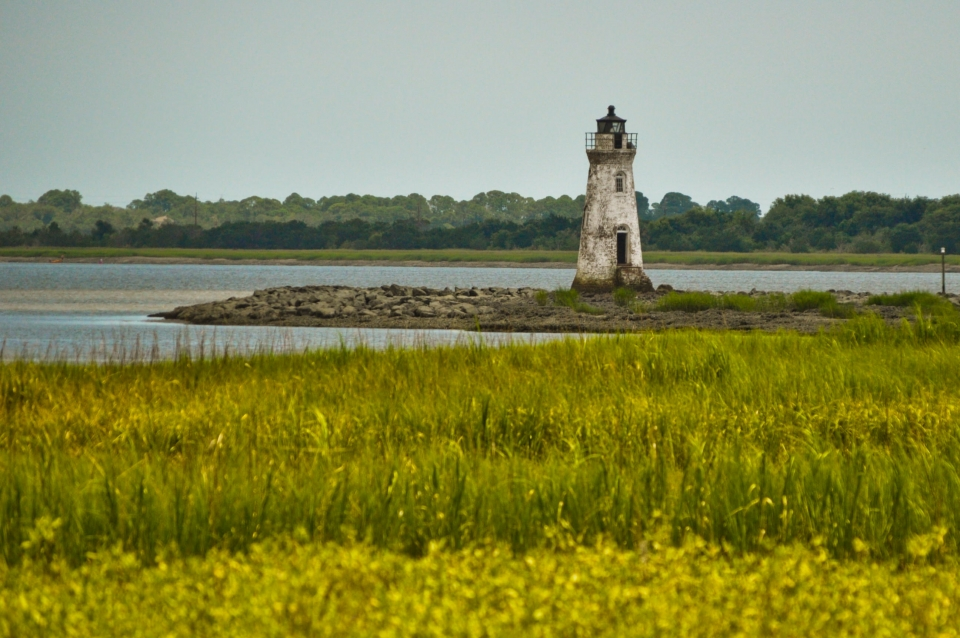Old lighthouse tower on a rocky projection into water with a field of grass at Fort Pulaski National Monument