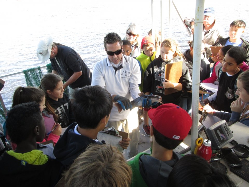 Man holding a fish in both hands showing young students on a boat
