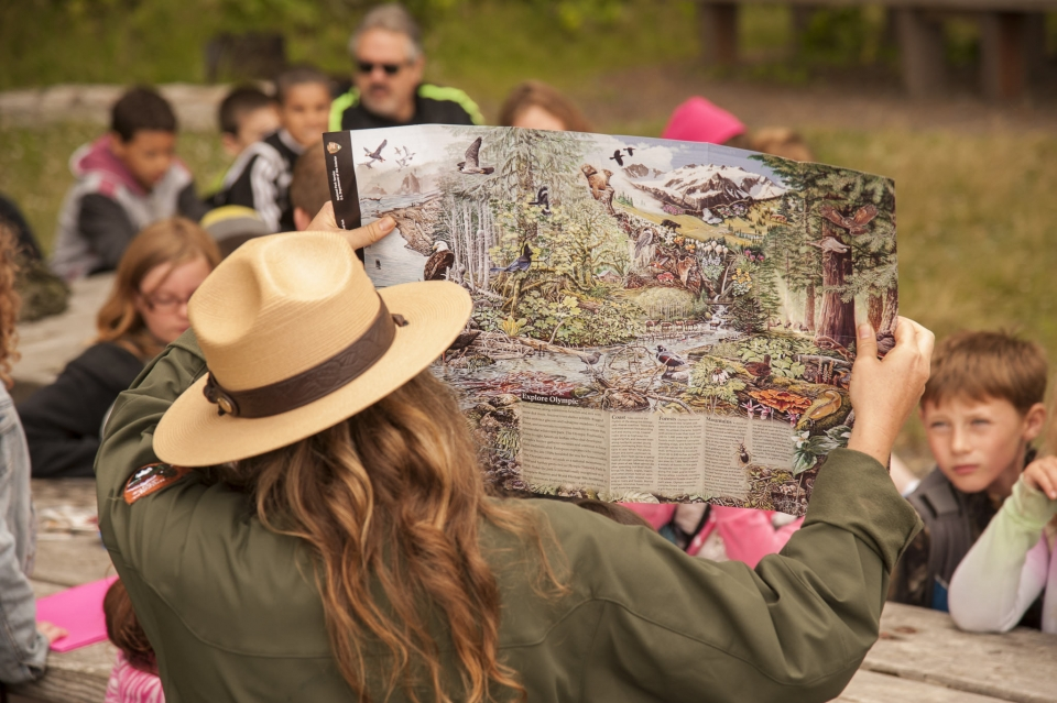 Back of a park ranger holding up a park map with wildlife on it to kids in the audienceo