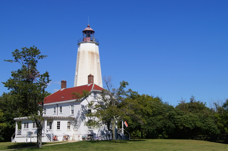 White house with lighthouse tower behind is surrounded by trees with blue skies at Gateway National Recreation Area