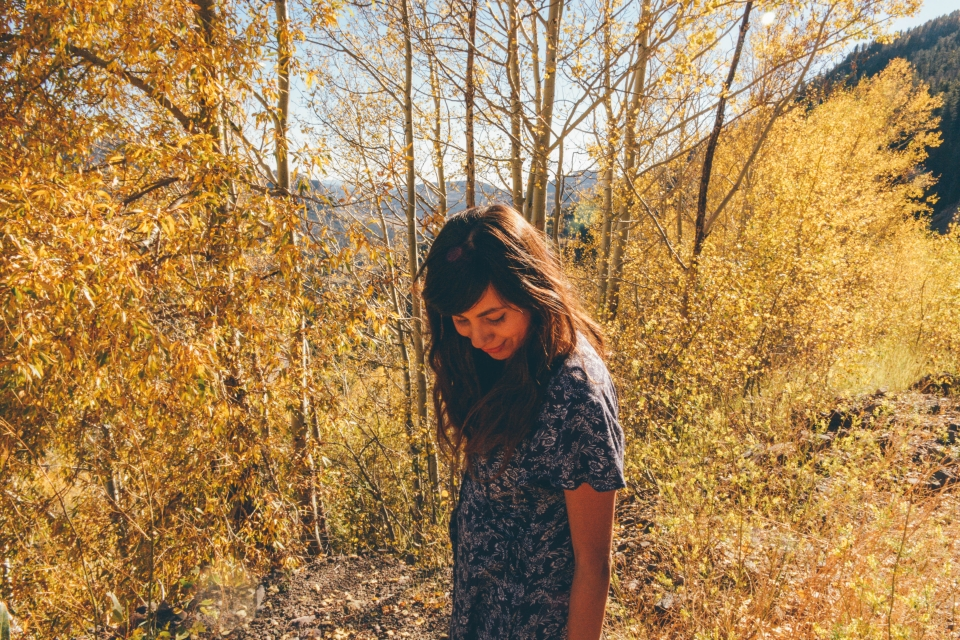 Grace standing in trees with yellow leaves