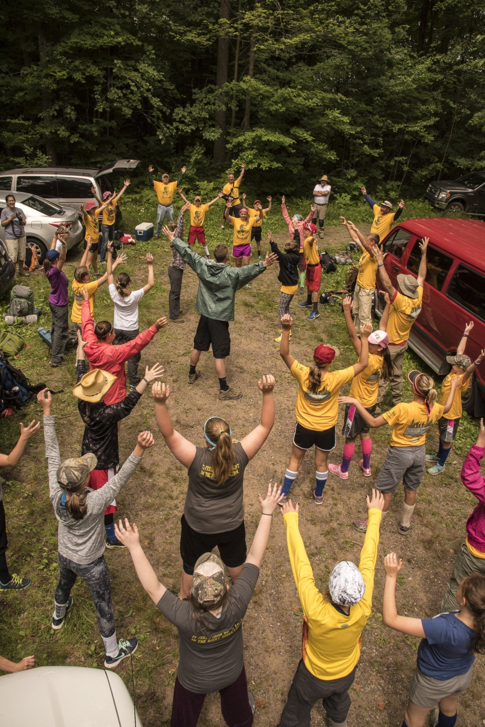 Group of youth in the wilderness with both hands raised