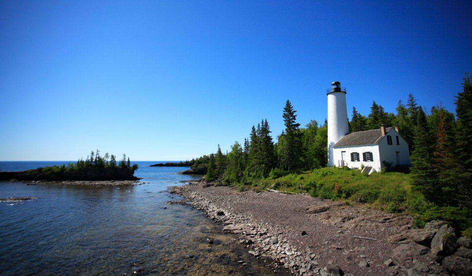 Lighthouse on a rocky seashore with evergreen trees around it at Isle Royale National Park