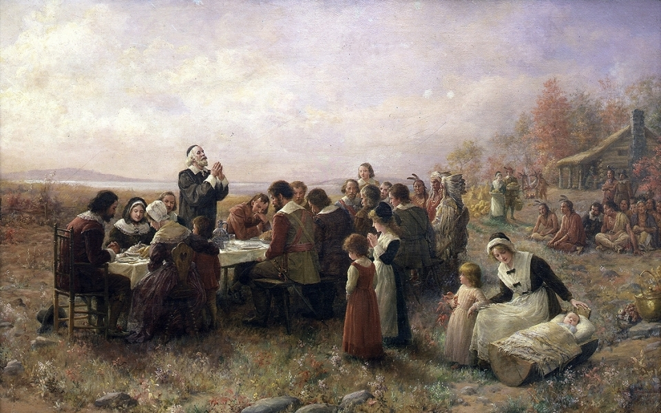 "Jennie Augusta Brownscombe's oil painting ""The First Thanksgiving at Plymouth\"" with colonials and Native Americans gathered around a table for a meal"