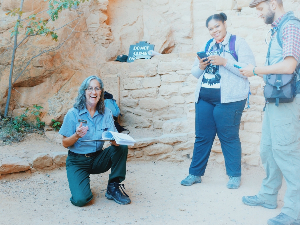 Park ranger on one knee smiling at camera with two other people standing next to her