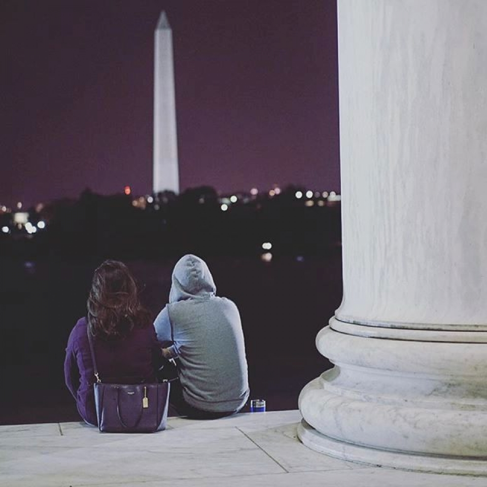 Two tourists looking at the Washington Monument at night