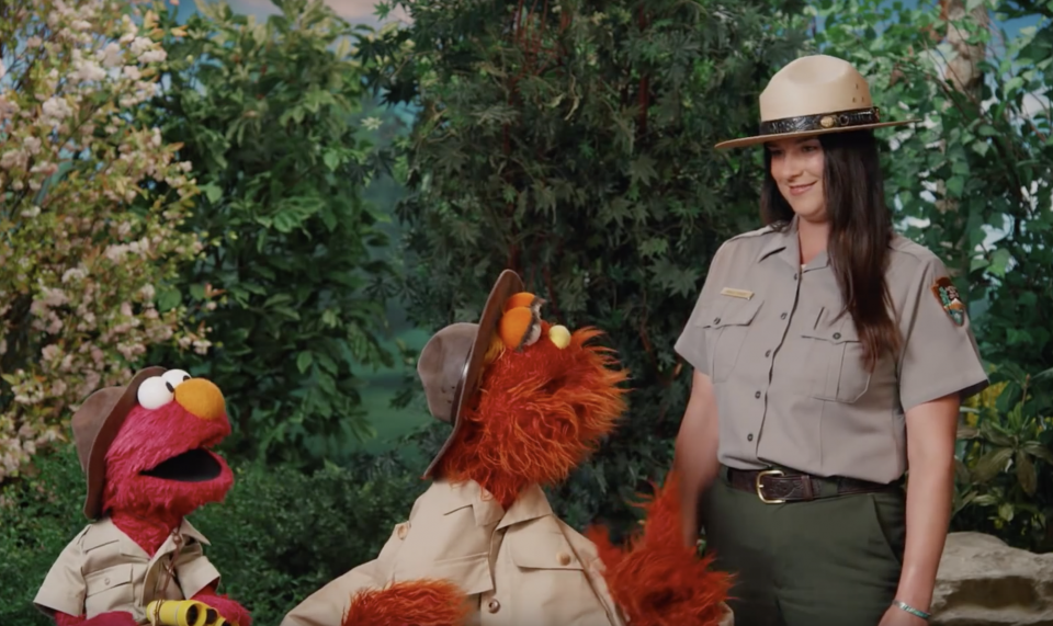 Muppets Elmo and Murray talk to a park ranger