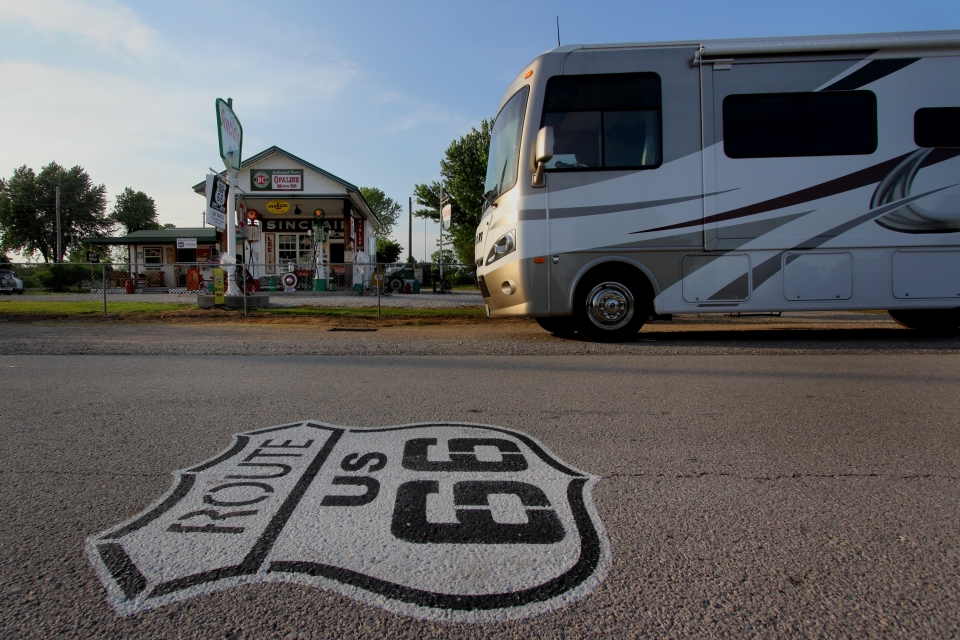 Route 66 sign painted on street, motorhome and gas station in background