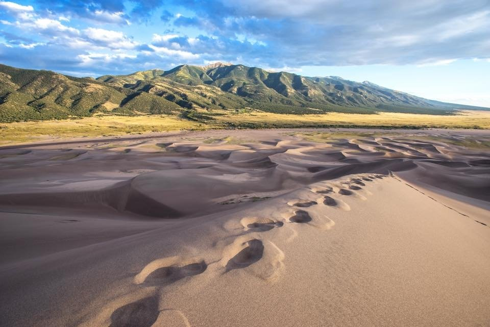 Footsteps in sand dunes with hills in the background