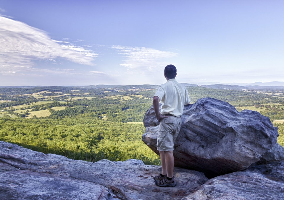 Man standing next to a big boulder looking down to the Shenandoah Valley