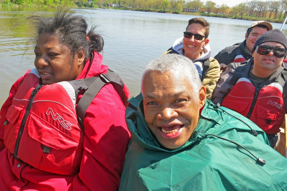 Diverse group of adults with developmental disabilities in canoe smiling at camera