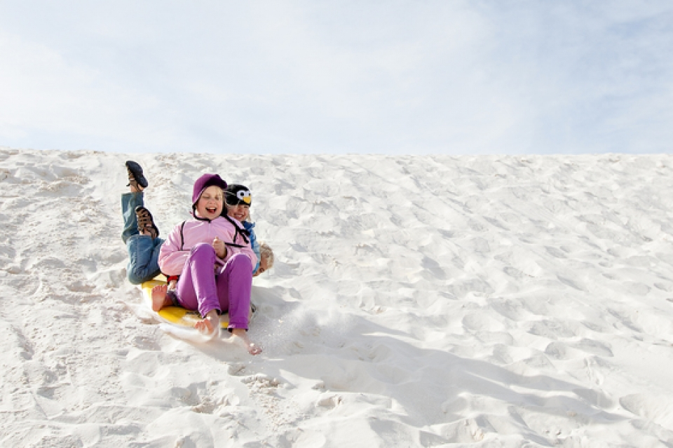 Two children sledding down white sand dunes