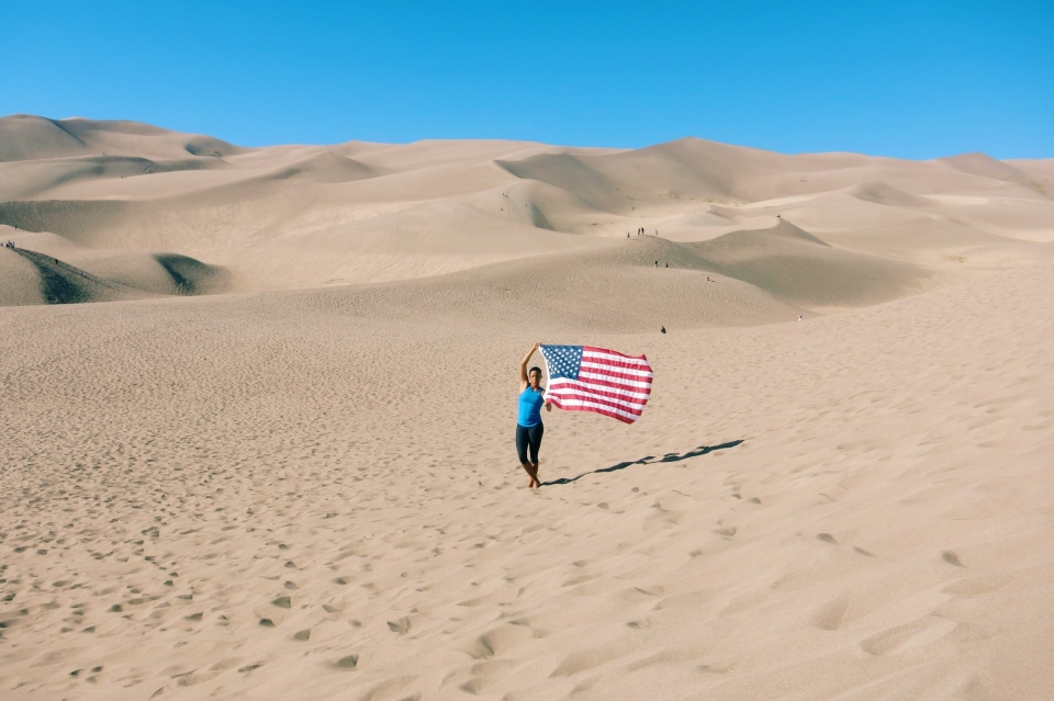 Whitney Mitchell holding waving American flag at Great Sand Dunes National Park and Preserve