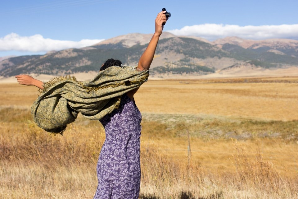 Back of woman with arms stretched out with hills in the background