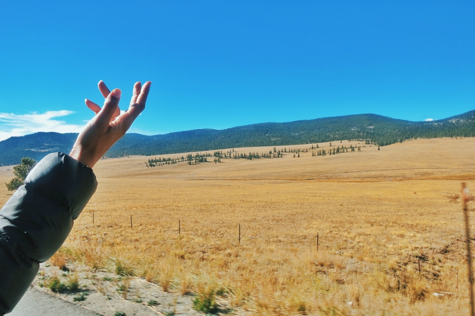 Hand reaching towards the sky with open landscape in the background