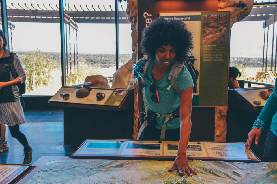 Whitney looking at a 3-d topo map in visitors center