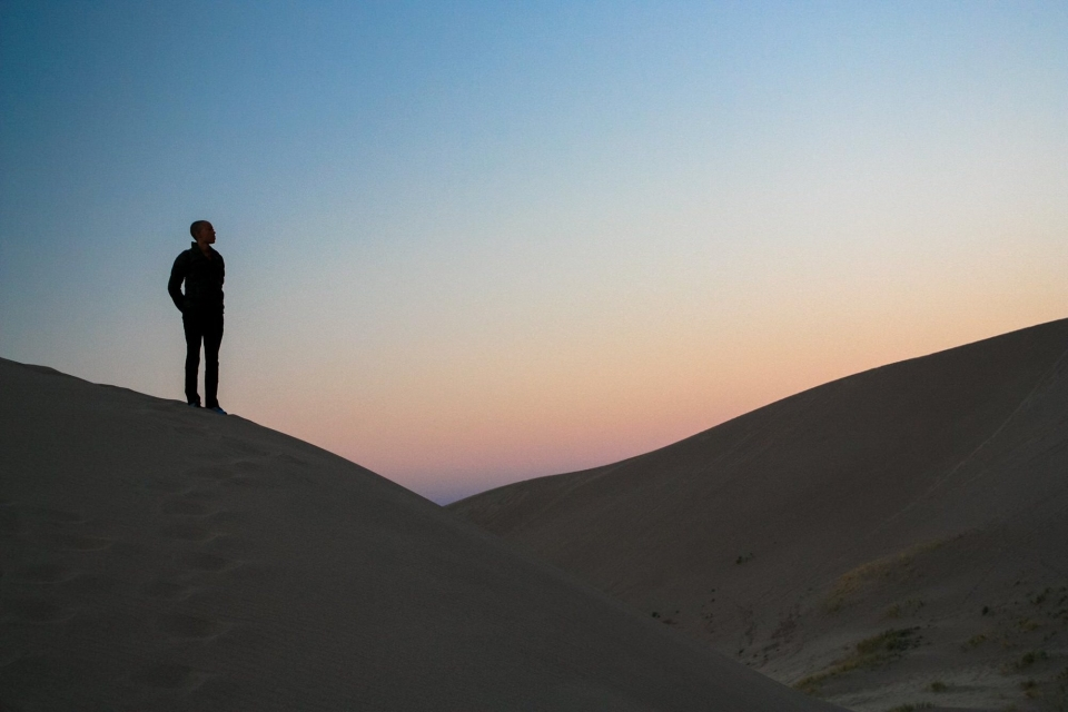 Andia Winslow standing on the Great Sand dunes during dawn