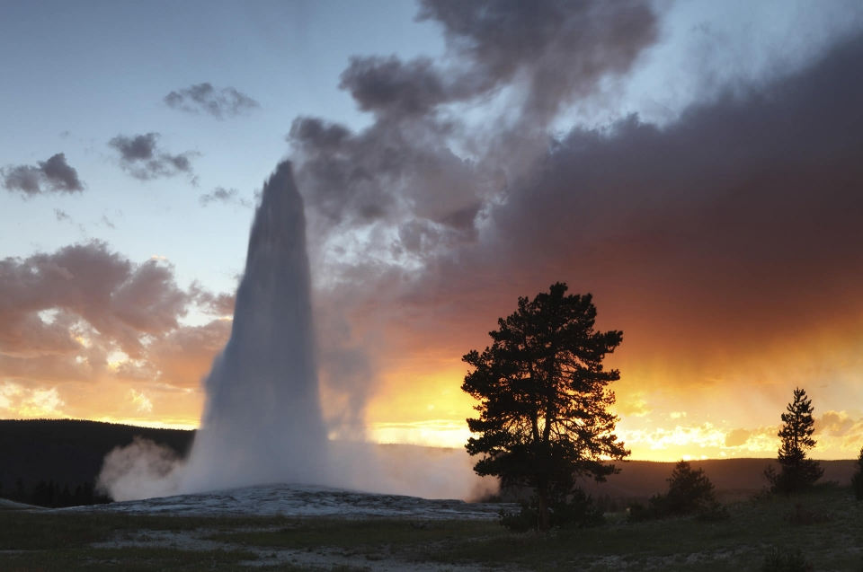 Old Faithful goes off at sunset in Yellowstone