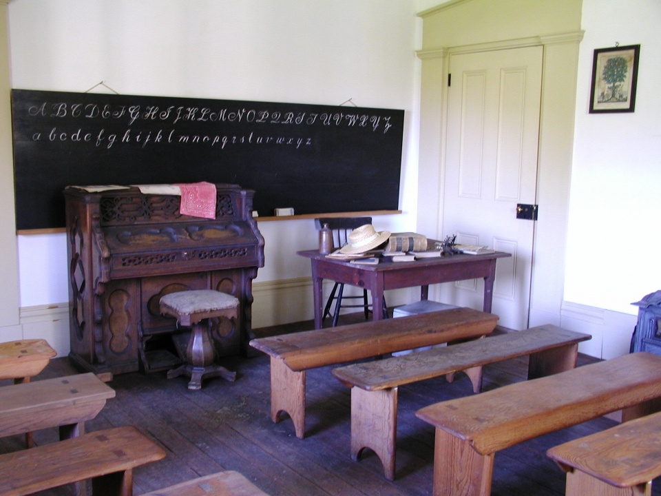 Wooden benches lined up to face a piano, a desk, and a chalkboard listing the alphabet in cursive lettering; a recreated classroom exploring early education at Storer College; Harpers Ferry National Historical Park