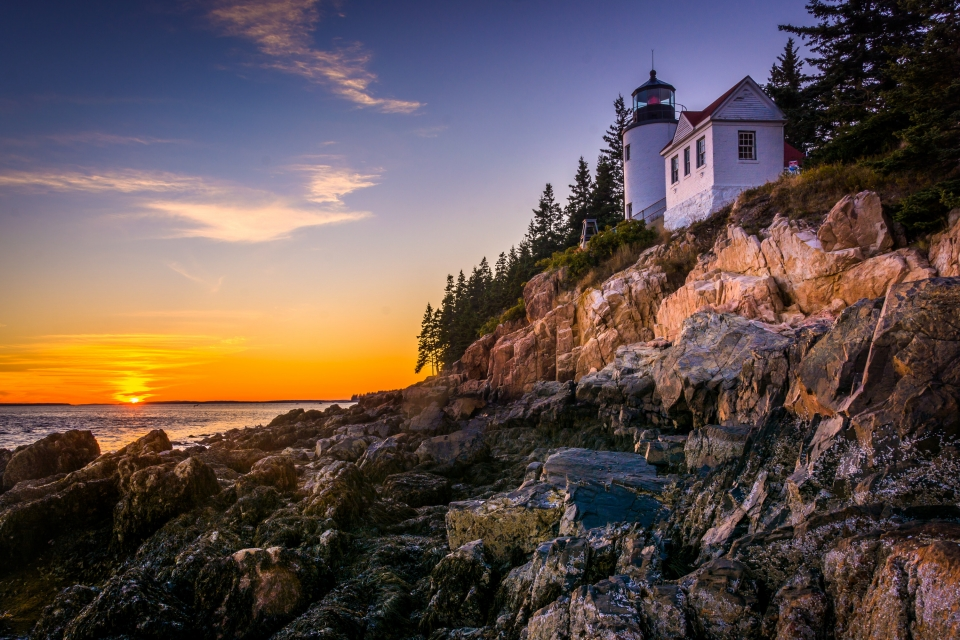 Sun rising over the ocean in the horizon, lighting up the rocky shore with a white lighthouse at Acadia National Park