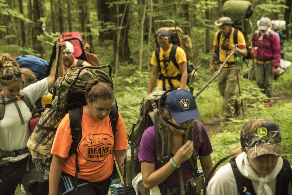 A group of youth hiking through the green forest of Ice Age National Scenic Trail