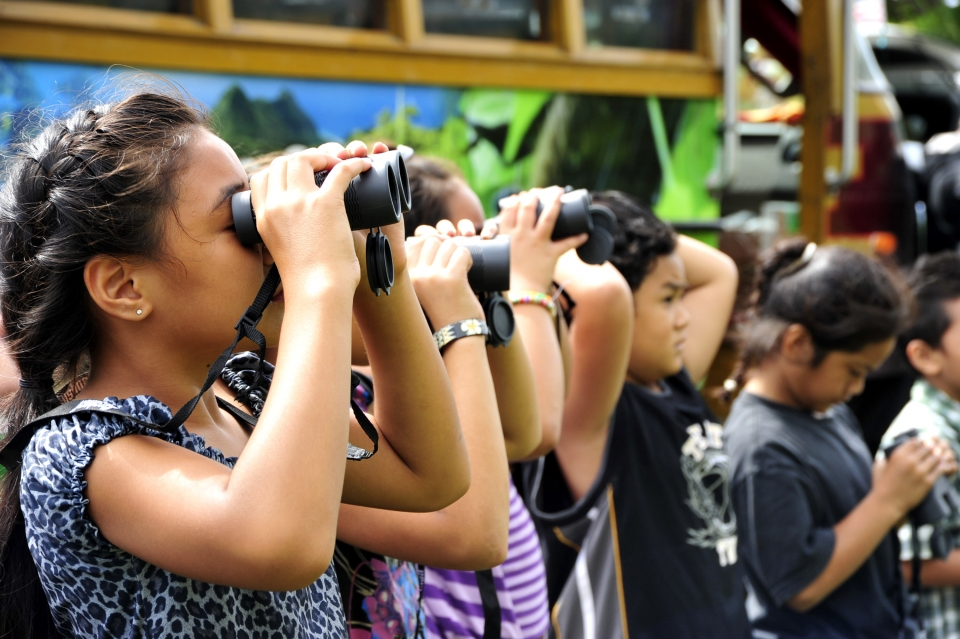 A group of elementary school students look through binoculars during a bird watching experience at National Park of American Samoa