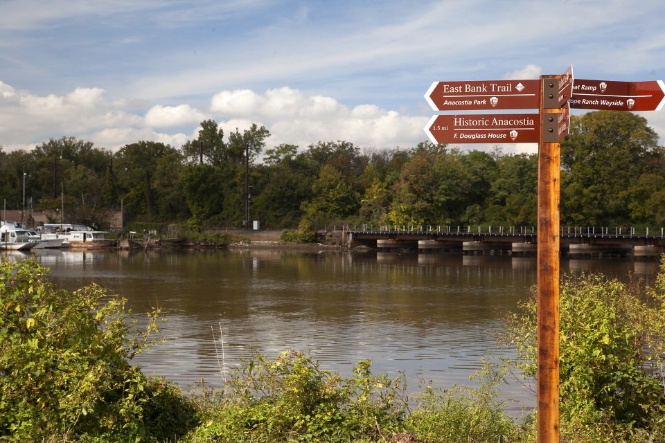 Paved walkway along the Anacostia River with a signpost directing to landmarks in the park