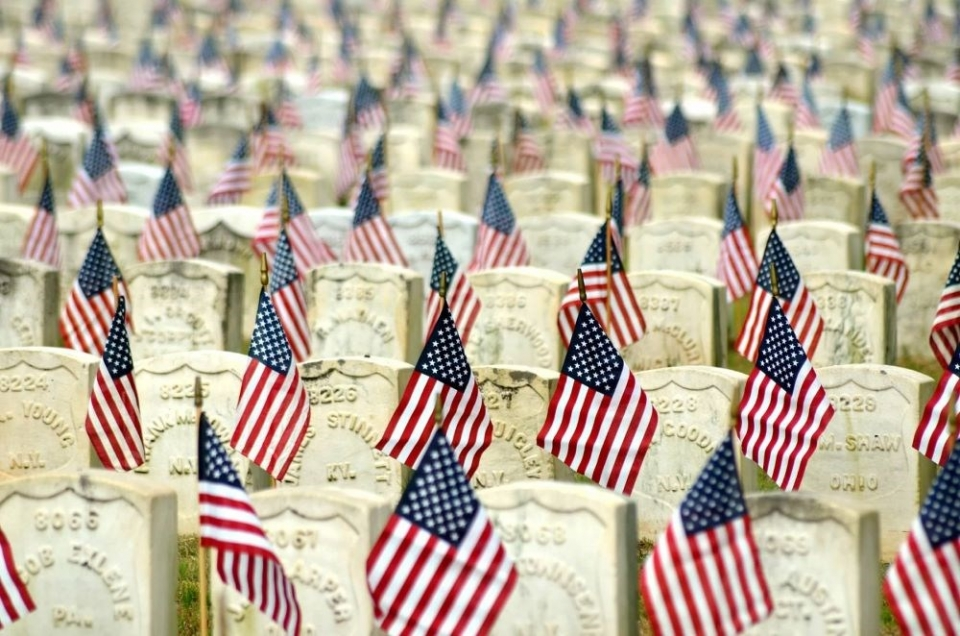 Rows of stone graves decorated with small American flags