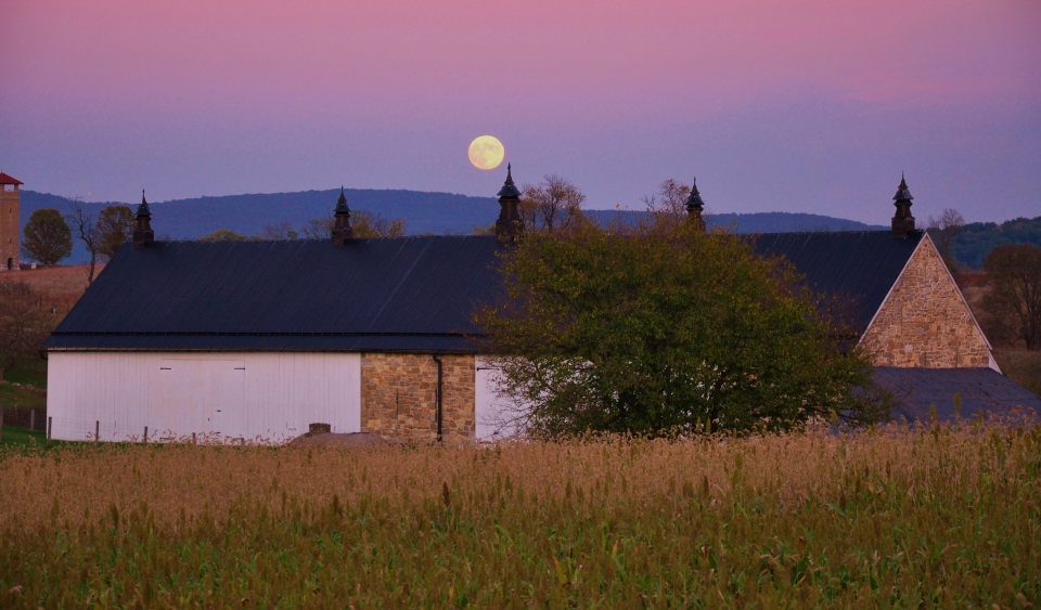 Within a blue and purple sky, the moon stands above the Antietam National Battlefield.