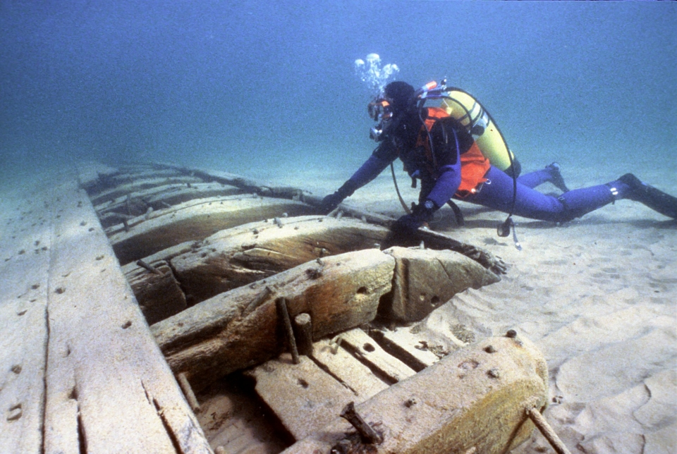 A scuba diver in orange and blue looking at the remnants of the wooden schooner Noquebay at Apostle Islands National Lakeshore
