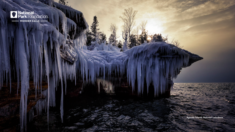 Icicles drop down over a stony cliff into a cold great lake underneath