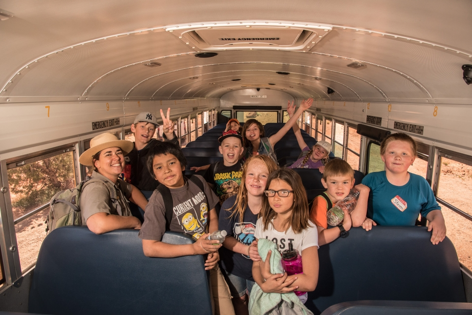 A group fo students and a park ranger in a school bus at Arches National Park