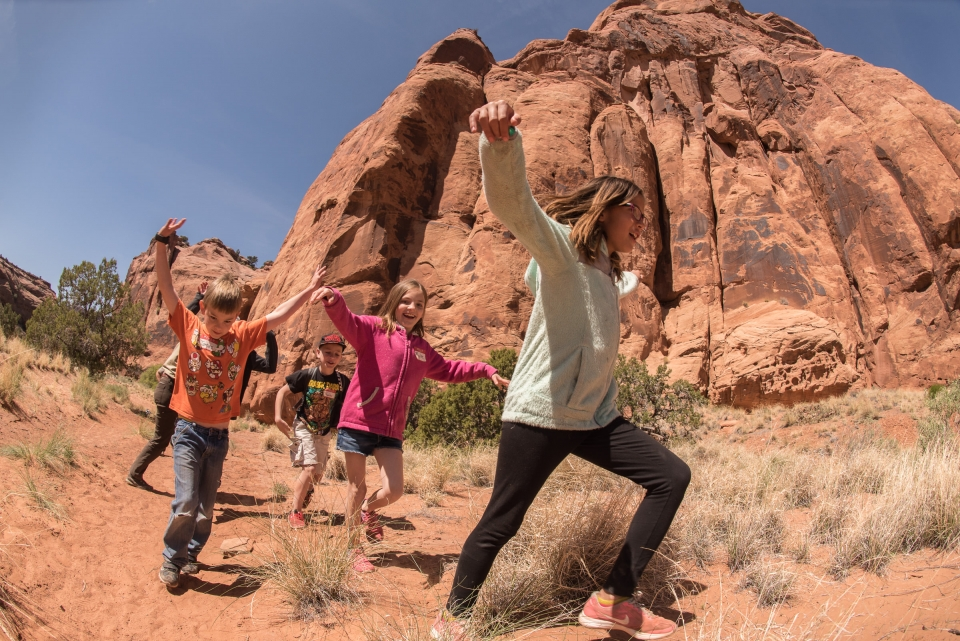 Happy children running outside amongst the red sandstone formations at Arches National Park