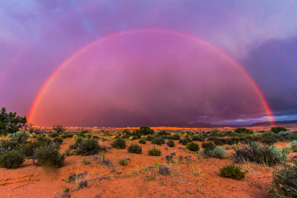 Full half-rainbow with a faint outer rainbow over the desert landscape at Arches National Park