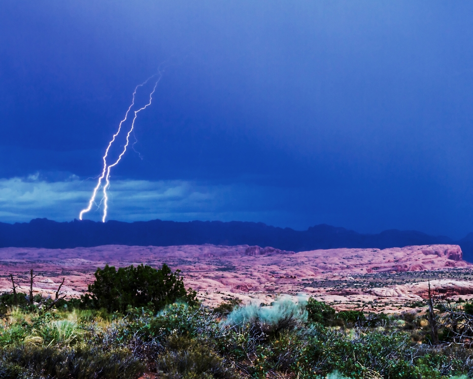 Double lightning striking the ground behind the desert landscape of Arches National Park