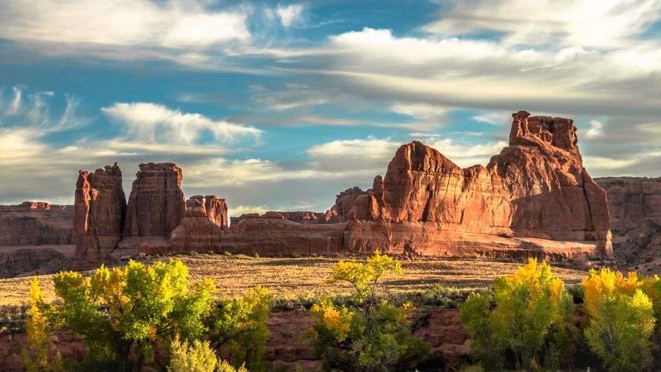 Golden sunlight illuminates an expansive panel of rock. Picturesque clouds float in the sky, and in the foreground, light green plants flourish