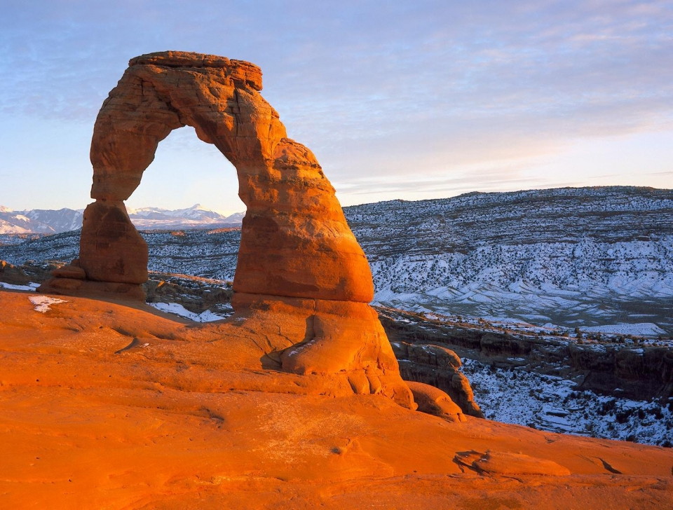Delicate Arch rock formation from distance appearing red against snow-covered slopes at Arches National Park
