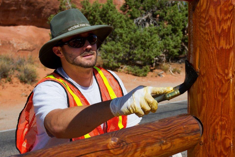 A maintenance worker, in a high-visibilty vest, stains a fence at Arches National Park