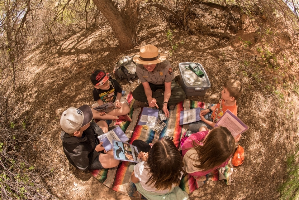Seen from above, five students sit on a blanket with a park ranger in a circle. Around then are their backpacks and school materials.