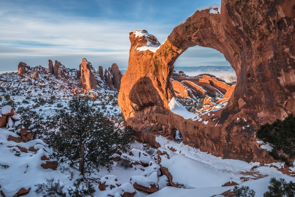 A light snow dusts the red stone arches and surrounding landscape