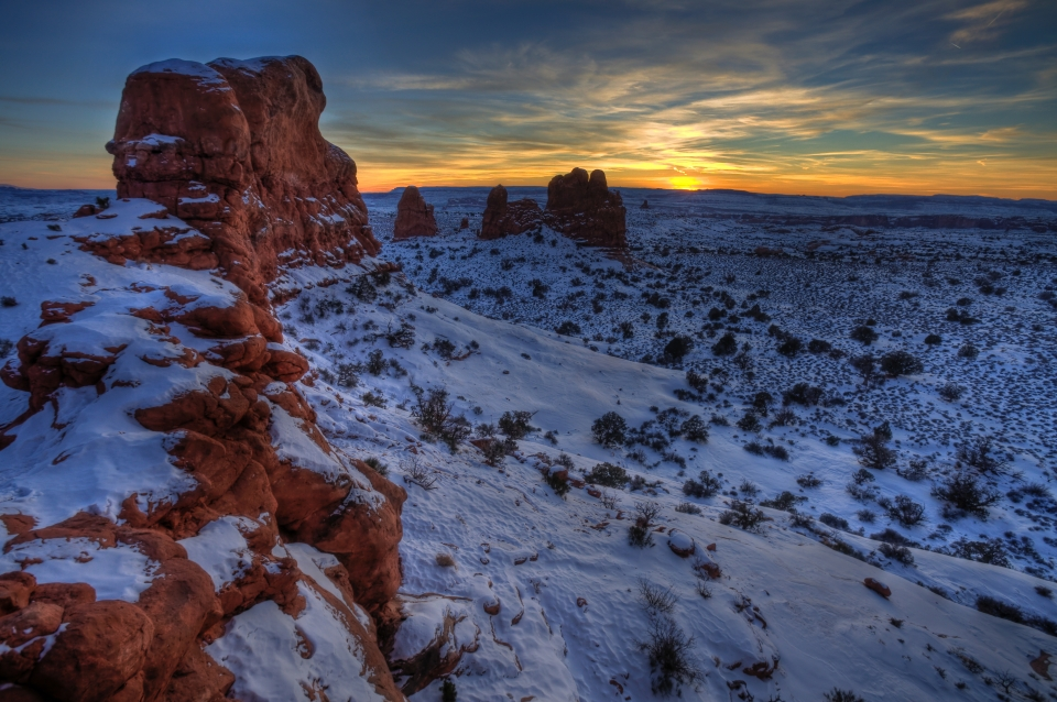 The colorful orange sun setting in the horizon of a snowy Arches Natoinal Park