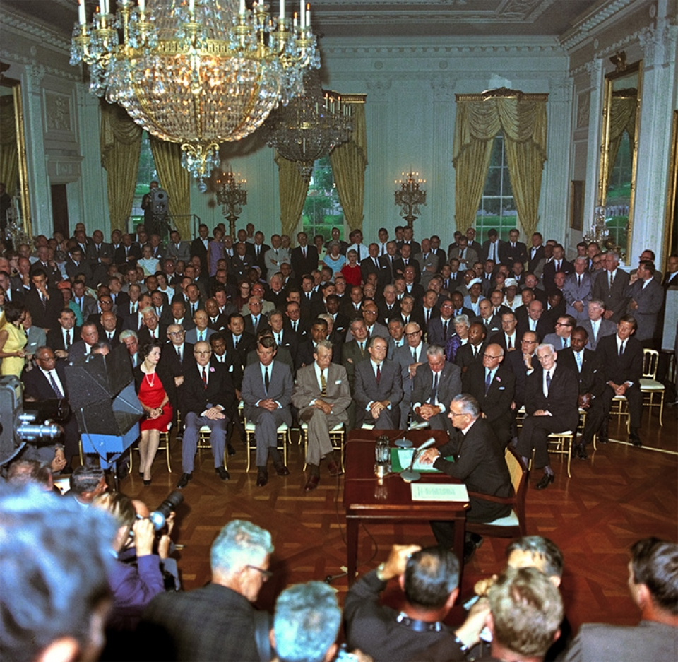 Colored photo of a room filled with seated people as the Civil Rights Act of 1964 is being signed.