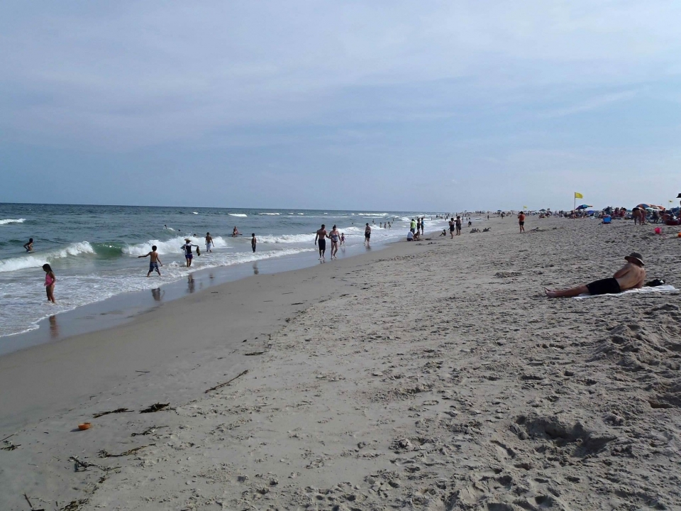 Many people at the white sandy beach at Assateague National Seashore on a sunny day