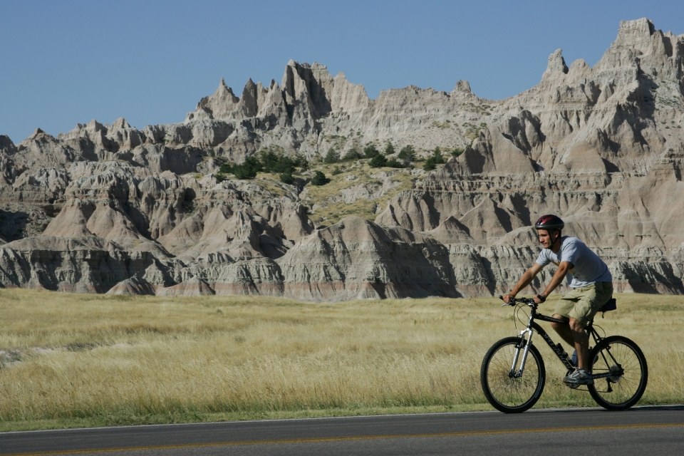 A man wearing khaki shorts and a grey t-shirt on a mountain bike on a paved road in front of the brown and grey cliffs of Badlands National Park