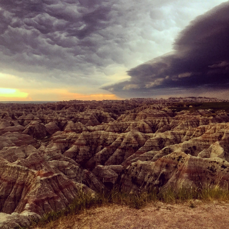 Dramatic storm clouds rolling with the sun in the horizon over the black and white sandstone landscape at Bandlands National Park
