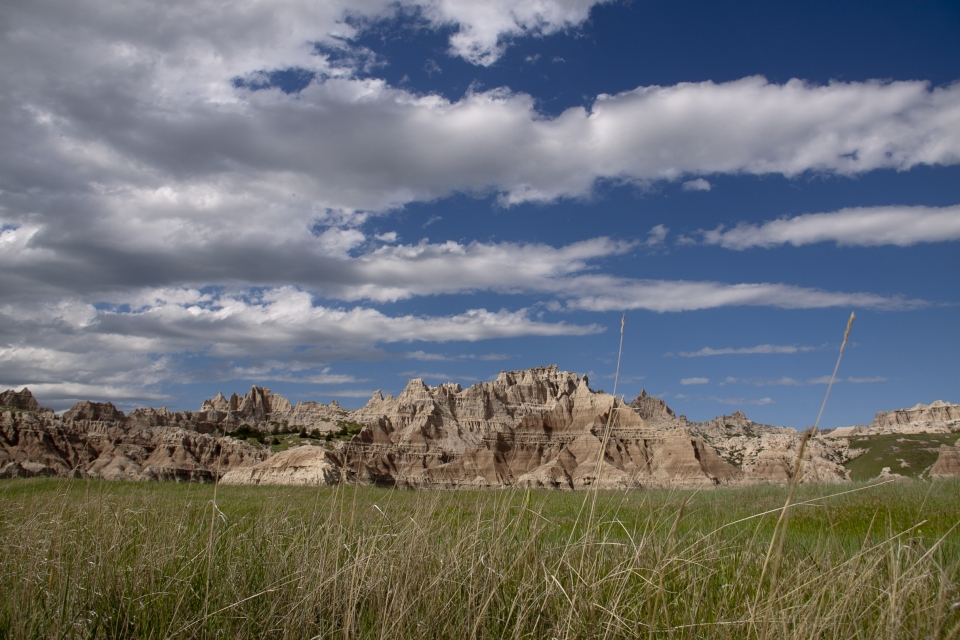 Partly cloudy sky over the prairie and colorful geological formations at Badlands National Park.
