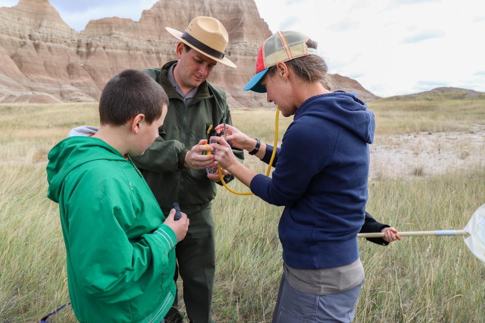 A national park ranger, a teacher, and a student, inspecting a specimen under a field microscope in the prairies of Badlands National Park