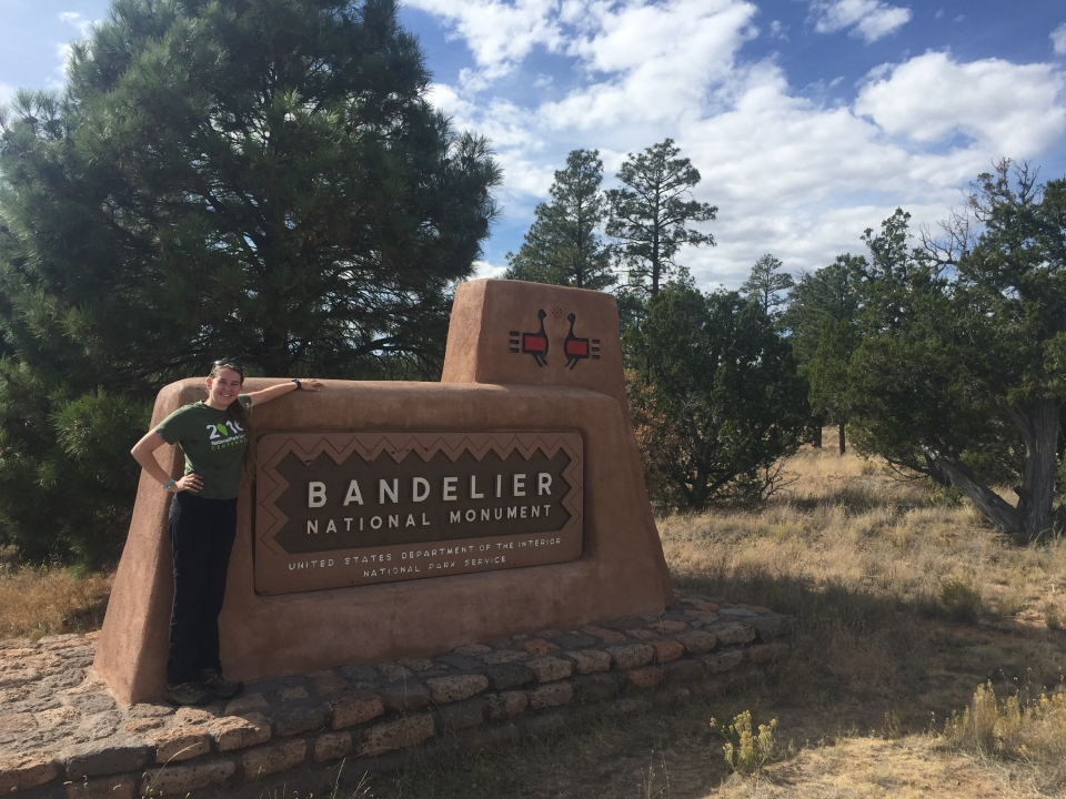 Riley Hays standing beside Bandelier National Monument park sign