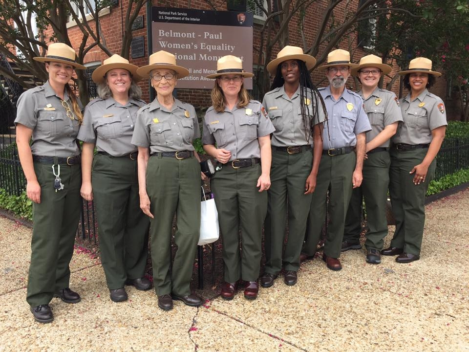 Eight diverse National Park Service rangers standing in front of the Belmont-Paul National Monument sign